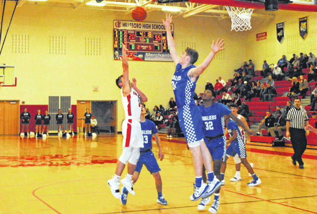 Hillsboro's Gavin Temples floats a shot over the outstretched hand of Chillicothe big man Brandon Noel on Tuesday at Hillsboro High School where the Indians hosted the Cavalier in FAC boys basketball action.