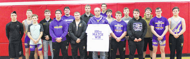 McClain Head Coach Shane Paul and his team pose for a group shot following Paul's 100th career win at Jackson High School on Thursday.
