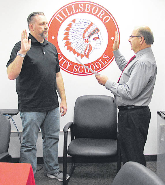 Bill Myers, left, is sworn in as the 2019 president of the Hillsboro City Schools Board of Education by Treasurer Ben Teeters during a board reorganizational meeting Monday evening.