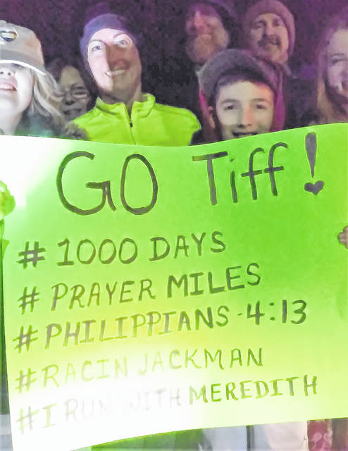 Shortly before midnight Friday, 30 of Tiffany Miller's closest friends gathered in the parking lot of Southern State Community College in Hillsboro to help the Fairfield school teacher celebrate 1,000 consecutive days of running. Shown, from left, are Anna Fleming, Tiffany Miller and Ethan Fleming holding a sign commemorating the event.