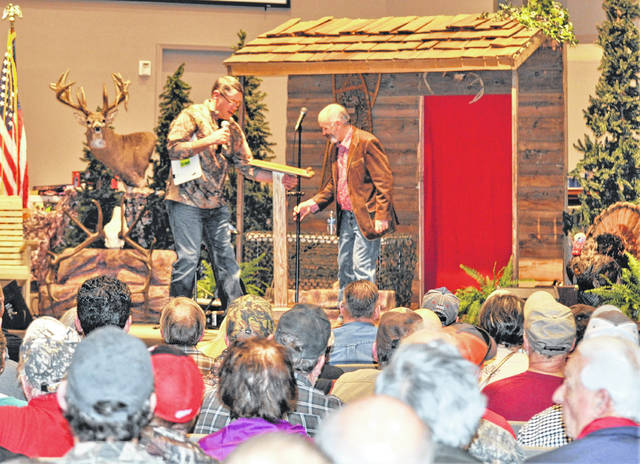 Hillsboro Bible Baptist Church Event Director Troy Putnam (on stage at left) introduces gospel singer Wade Spencer at last year's Sportsman's Night Out. The annual event will be Saturday, Jan. 26 at the church on SR 124 east of Hillsboro.