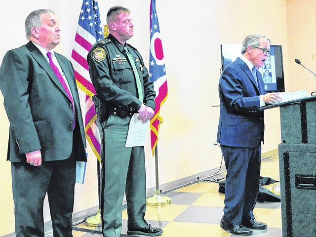 Ohio Attorney General Mike DeWine talks in front of a herd of media last year while announcing arrests in the murders of eight members of the Rhoden family in Pike County. He is flanked by Pike Sheriff Charlie Reader and Pike County Prosecutor Rob Junk.