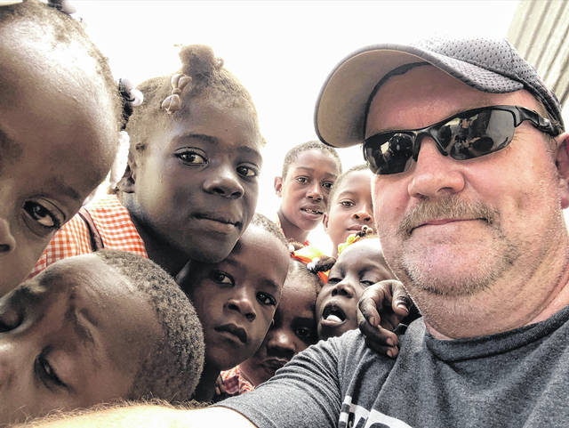Paint Creek Public Information Officer Branden Jackman, right, takes a selfie with a crowd of Haitian children recently. Jackman said most Haitian households do not have mirrors, so when someone has a phone with a front-facing camera, children flock to it to see what their faces look like.