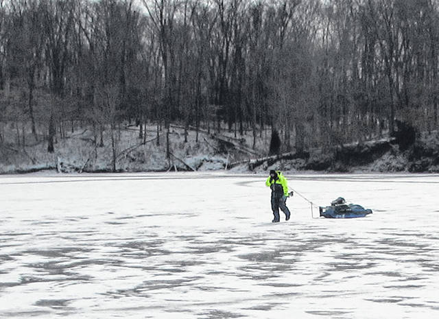 Josh Endsley of Bainbridge is shown pulling his ice fishing equipment across the frozen Rocky Fork Lake on Thursday.