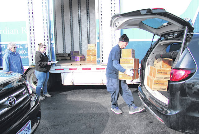 Local Girl Scout Product Sales Coordinator Marcia Williams (far left) and Girl Scout Volunteer Brenda Tompkins (closest to Williams) look on as delivery personnel load boxes of cookies into vehicles Thursday morning at Jerry Haag Motors in Hillsboro.