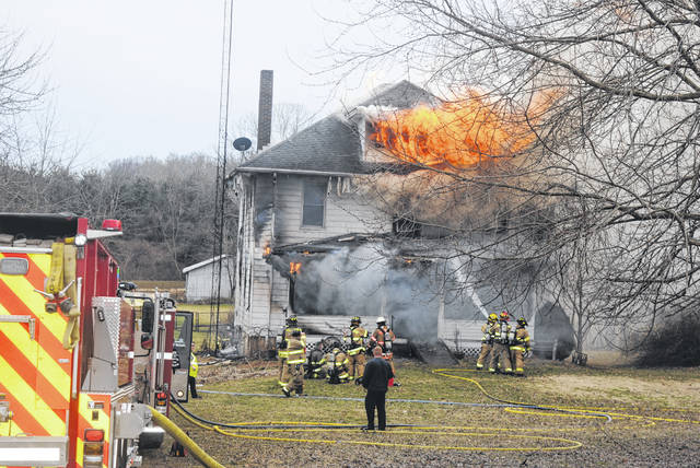 Crews battle a house fire on U.S. Route 50 east of Hillsboro Tuesday afternoon. No one was home at the time of the fire, officials said.