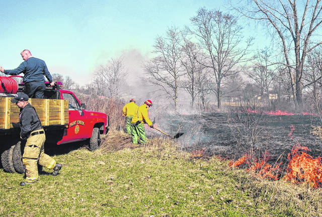 Firefighters work to extinguish a field fire on March 6 last year at a property on U.S. Route 50 near Hoagland. The fire was reportedly caused by a burning couch.