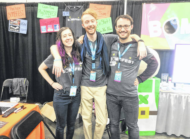 McClain High School graduate Marisa Hike (left) is pictured with Zachary Pierce (center), the lead developer for the new video game Bombfest, and Matthew Trowbridge, the game's sound effects artist. They are shown showcasing the game at the Game Developers Expo (GDEX) in Columbus, where they won the Crowd Favorite Award.