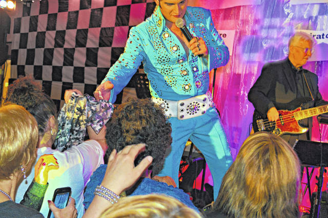 Elvis impersonator Tyler Christopher hands a scarf to the crowd during his performance last year at the Highland County Senior Citizens Center in Hillsboro.
