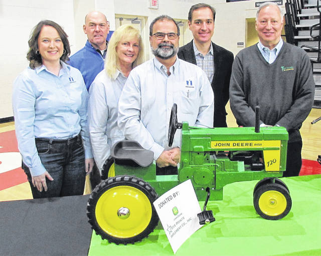 Russ Newman of Newman Insurance Agency purchased a John Deere 720 pedal tractor in an auction at the close of the Ag is Everyone's Business seminar held Friday at the Patriot Center at Southern State Community College. The pedal tractor was donated by Five Points Implement Company of Hillsboro. The high bid was $950 and will benefit the FFA chapters of the five Highland County public school districts. Newman is shown in the center with members of his staff. Keynote speaker for the event Mark Gold is at the right.