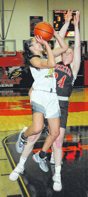 Lynchburg-Clay senior Peyton Scott muscles her way to the basket against a bigger Nelsonville-York defender on Thursday at Waverly High School where the Lady Mustangs battled the Lady Buckeyes in a D III Southeast District Semi Final tournament game.