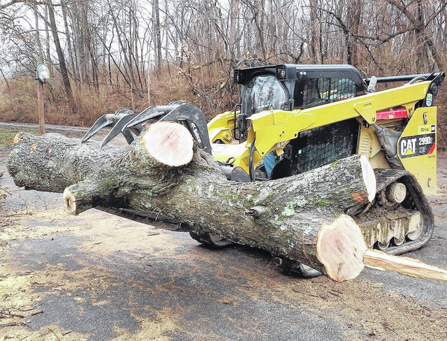 Mark Cooper, an equipment operator for Rocky Fork State Park, is shown bringing wood into the collection area of the old basketball court, just off the main entrance from North Shore Drive.
