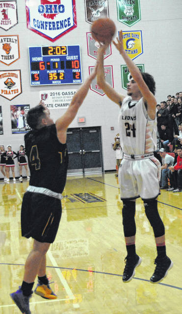 Fairfield's Wyatt Willey attempts a pull up jumper over a St. Joseph defender on Tuesday night at Northwest High School where the Lions battled the Flyers in a D IV Southeast Sectional Final tournament game.