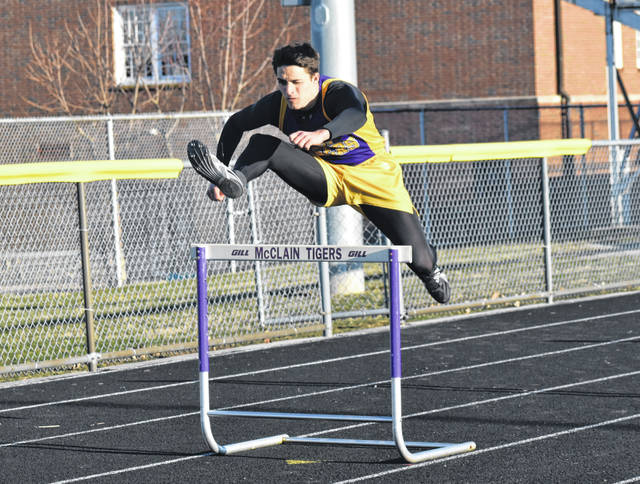 McClain's Blake Gall clears a hurdle on Tuesday at McClain High School during the boys 300-meter hurdles during a dual meet with the Circleville Tigers.