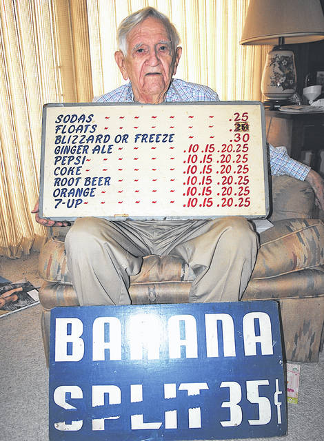 Howard Ellis is pictured in his Hillsboro home with a pair of signs that were in use at the Dairy Queen in Hillsboro around 1953 or 1954.