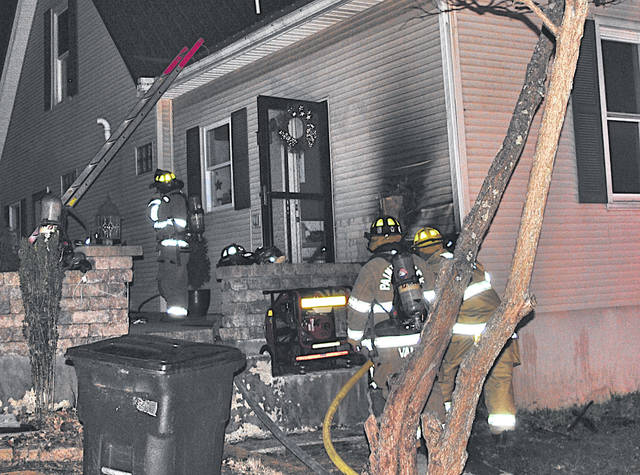 Firefighters search for the origin of a fire Thursday night at the rear of a residence at 835 W. Walnut St. in Hillsboro.