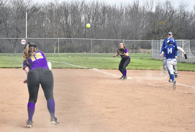 McClain's Beckley Smith throws across the diamond to Kaleigh Easter at first base on Wednesday at Mitchell's Park in Greenfield where the Lady Tigers battled FAC rivals the Lady Blue Lions of Washington High School.