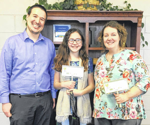 Matalyn Magee, center, and her teacher, Angela Buller of Lynchburg-Clay Elementary, right, are pictured being awarded the first prize in the 2019 Recycling and Litter Art Contest from Clinton Davis of Highland County Community Action representing the Highland County Recycling and Litter Program and the RPHF Solid Waste District.