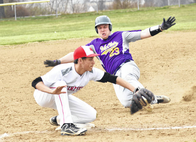 McClain's Cody Pollock slides into third base on Saturday at Mitchell's Park in Greenfield where the Tigers hosted the Fairfield Lions in a cross-county rivalry baseball game. Nathan Vidourek attempts to catch the ball and guard the bag for the Lions.