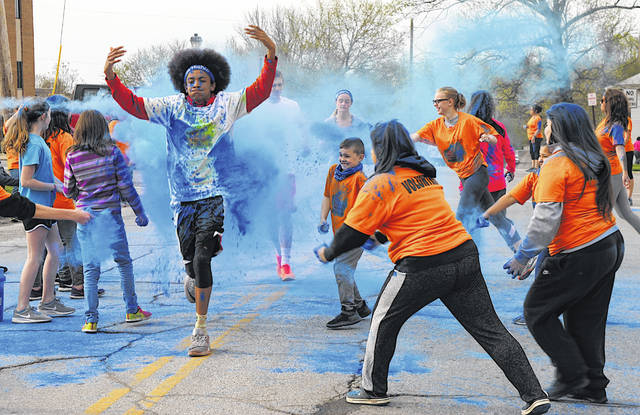 Runners on South West Street in Hillsboro are splattered with color during the Highco Dash for DD 5K Color Run/Walk held Saturday.