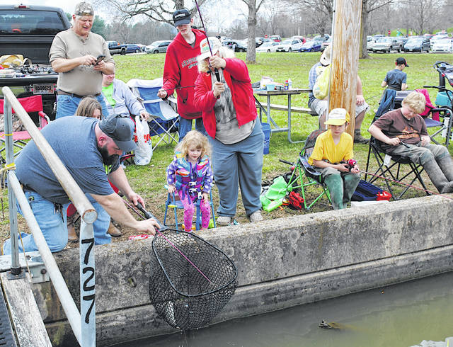Hillsboro resident Anthony Garretson, left, helps 3-year-old Violet Nihart of Wilmington net a trout she reeled in Saturday during the Highland County Rod & Gun Club's annual Trout Derby at Rocky Fork Lake.