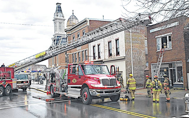 Firefighters are pictured in front of a building on Jefferson Street in Greenfield that caught on fire Saturday afternoon.