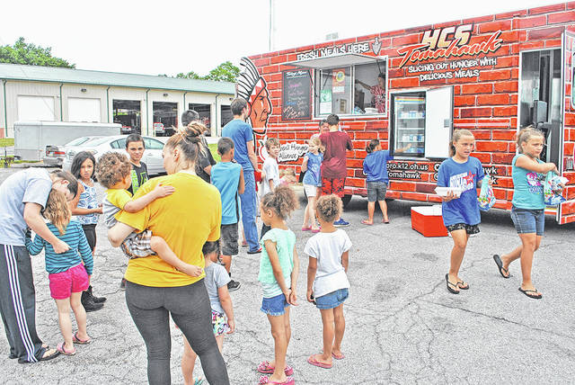 People are lined up last summer behind the Paint Creek Joint EMS/Fire District location in Hillsboro at one of the Hillsboro City Schools Tomahawk food truck summer feeding program stops.