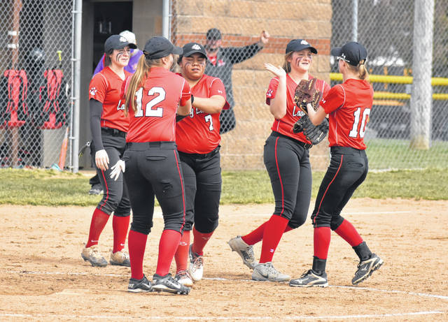 The Fairfield Lady Lions infielders celebrate with starting pitcher Kaiti White (7) after a strike out against the McClain Lady Tigers on Saturday, April 6, at Fairfield High School.