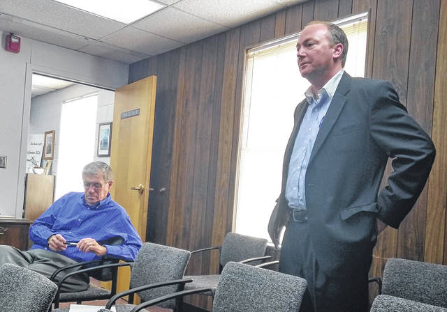 Ohio Gov. Mike DeWine's Southwest Regional Liaison Jason Gloyd, standing at right, is shown speaking to Highland County commissioners on Wednesday. Also shown is county Auditor Bill Fawley, seated at left.