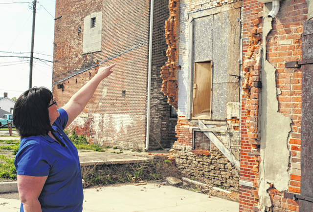 Jeretta Barr, one of the co-owners of Momma's West Main Cafe, gestures toward the rear of a block of buildings owned by Jack Hope recently deemed uninhabitable. Barr and others have disputed the city's finding that the Momma's building is uninhabitable.