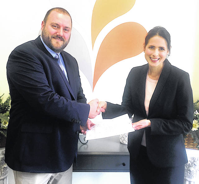 Anthony DeBord, left, community and customer experience account manager with AEP Ohio, recently presented Cara Dingus Brook, right, president and CEO of the Foundation for Appalachian Ohio (FAO), with the first installment of a $1 million gift to support education and environmental stewardship in Appalachian Ohio through FAO's Pillars of Prosperity. The gift, first announced in November 2018, will specifically support the expansion into the region of First Book, a nonprofit providing low-cost and high-quality educational materials to children, as well as an annual grant-round in environmental stewardship open to the 32 counties of Appalachian Ohio. The gift will also grow FAO's permanent endowment funds for education and environmental stewardship.