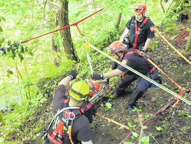 Rescue personnel are pictured at a scene Monday on Cave Road where a body was found at the bottom of a 70- to 80-foot cliff.