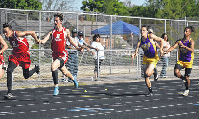 Hillsboro's Taylor Lucas and McClain's Kobe Penwell hand off the baton to their teammates Anthony Richards and Patrick Fout on Wednesday at Chillicothe High School where the the all six schools in the Frontier Athletic Conference gathered for the FAC Track and Field Championship Meet.