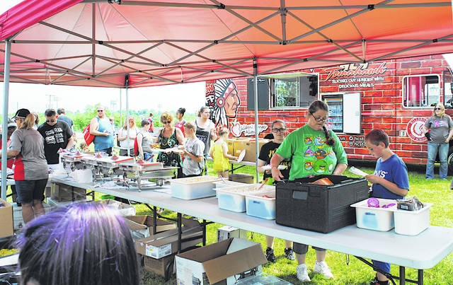 With the Hillsboro City Schools Tomahawk food truck in the background, local residents line up for free food Friday at the old Hillsboro High School site during the kick off for the school district's summer food program.