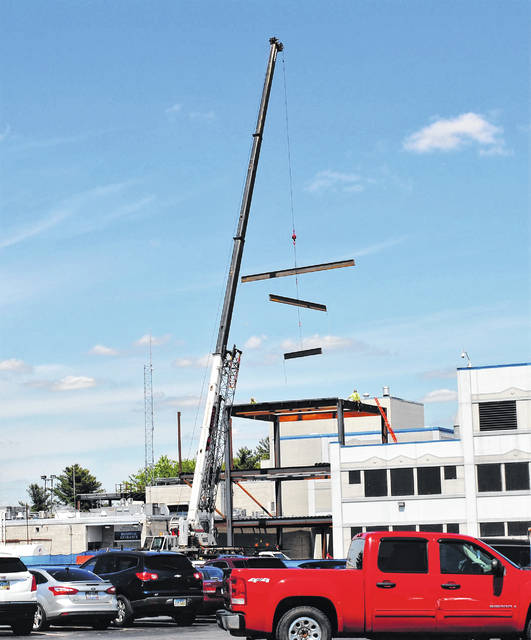 A tall crane moves steel pylons Monday afternoon at Highland District Hospital on North High Street.