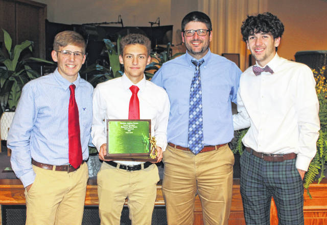 Representatives from the Hillsboro High School varsity Baseball team show off the teams 2019 FAC Championship plaque on Monday at the FAC Spring Sports Banquet in Washington Court House on Monday. Pictured (l-r): Grant Crum, Ethan Humphries, Head Coach Matt Garman and Luke Magulac.