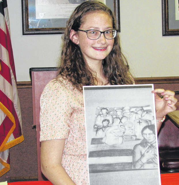 Sixteen-year-old Isabella O' Madden holds her award-winning first place entry in the Young American Creative Patriotic Art Contest, held Thursday at VFW post 9094 in Hillsboro.