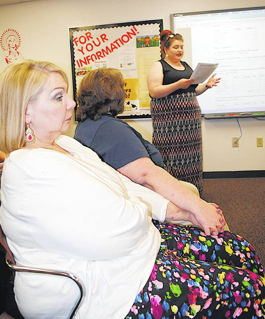 Liz Odland, left, a music educator in the Eastern Brown School District for 30 years, and Laura Pickering-Polstra hold hands Monday as Stephanie Hensley addresses the Hillsboro Board of Education. Pickering-Polstra and Hensley both questioned the board on its recent decision to consider the termination of suspended Hillsboro Choral Director David White's contract.