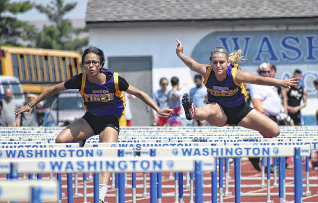 McClain's Zoe Rios (left) and Emma Stegbauer compete in the girls 100-meter Hurdle Finals at Washington High School on Saturday during the D II Southeast District Track and Field Championships.