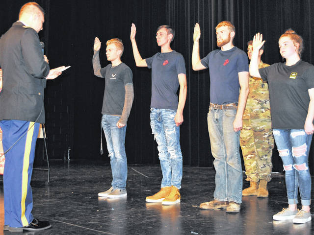 Four students commited to serving their country by formally taking the oath of enlistment Friday during a ceremony held at Hillsboro High School. Pictured, from left, are 2nd Lt. Alex Butler of the U.S. Army Reserves administering the oath to Cameron Moots, Zane Adams, Cory Mahan and Regan Claycomb.