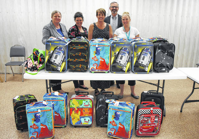 AT&T Pioneers, the philanthropic arm of the phone company's employees and retirees, on Thursday delivered a donation of suitcases for children removed from Highland County homes by Child Protective Services. Each suitcase comes with a blanket, toothbrush and toothpaste. Shown, from left, are Sarah Briggs, AT&T vice president of external affairs; Destiny Bryson of the Highland County Chamber of Commerce; Katie Adams, director of Highland County Job and Family Services; Mark Romito, AT&T director of external affairs; and Amanda Roades, foster care coordinator.