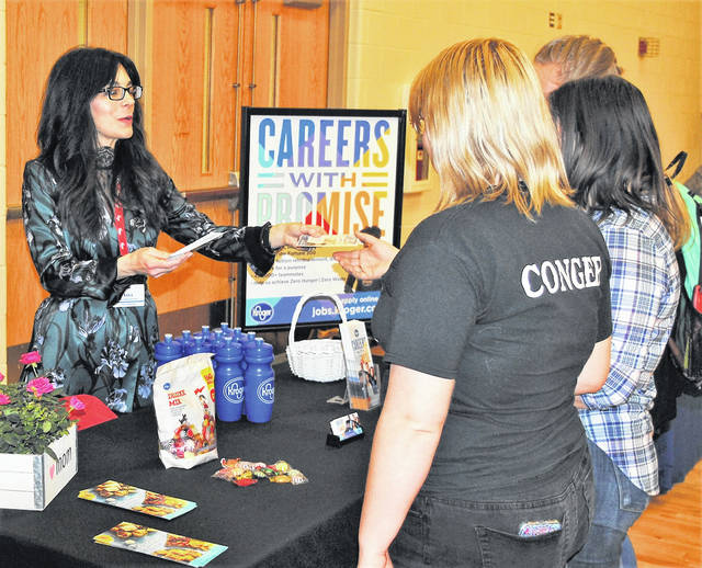 Lora Abernathy, assistant store manager for Kroger in Hillsboro, passes out employment opportunity information to students at the Hillsboro High School Senior Showcase Job Fair. Several area companies, educational institutions and service organizations were present at the second annual event.