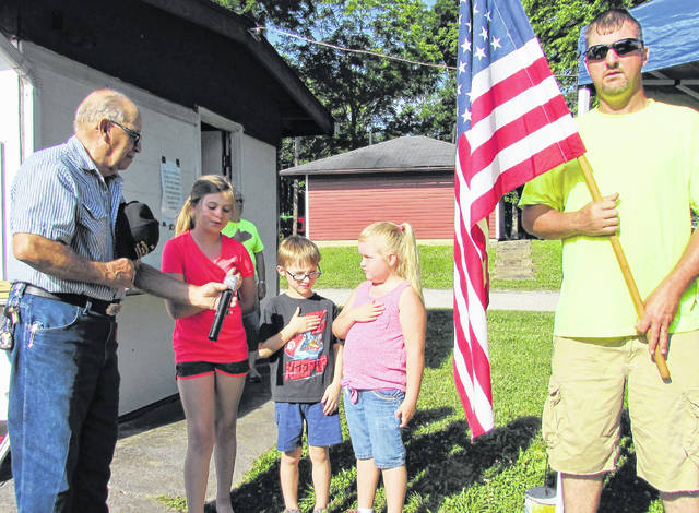 During the opening ceremonies for the 35th annual Highland County Antique Machinery Show, from, Delbert Morrow holds the microphone for Whitlee Morrow, Noland Cole and Olivia Cole as they recite the Pledge of Alliegiance to a flag, being held by Trent Morrow.