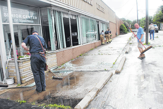 Emergency personnel and volunteers clean up glass after the majority of the front windows at the Highland County Senior Citizens Center were blown out during a storm Monday.