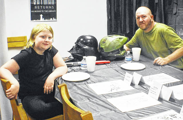 Sean Setty and his daughter, Kylie, enjoy complimentary snacks in the Highland County District Library's conference room as part of its third annual Comic Con.