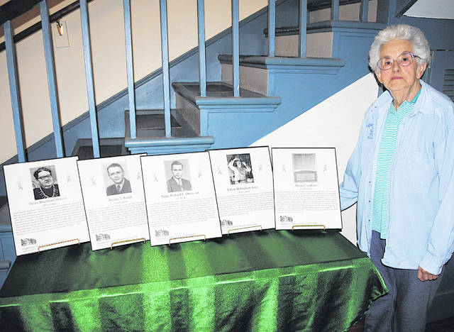 Local historian Jean Wallis stands next a display at the Highland House Museum of last year's inductees into the Highland County Historical Society Hall of Fame.