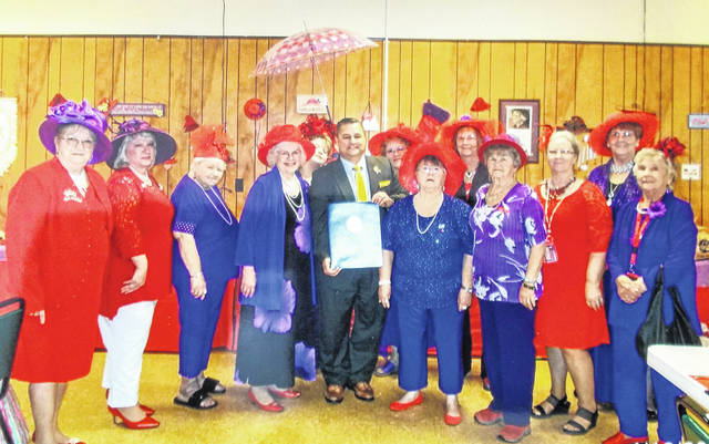 The Precious Pearls chapter of the Red Hat Society of Hillsboro was honored with a proclamation from State Rep. Shane Wilkin earlier this year, organizers said. Shown, from left to right, are Sharon Blevins, Iva Jean Savage, Carol Morris, Donna Sizemore-Haynes, Lori Morris (in back), Wilkin, Susan Thornhill, Patricia Zeisemer, Dolores Basford, Luise Curtis, Mary Reed, Linda Warnock and Norma Jane Morrow. April is the birthday month for the Red Hat Society, which boasts 35,000 members around the world. Red Hat members gather to enjoy dinner, shopping, games, visiting, prizes, entertainment, music, fun and dessert to celebrate. Those interested in the Red Hat Society can contact Queen Donna Sizemore-Haynes at 937-471-5027.
