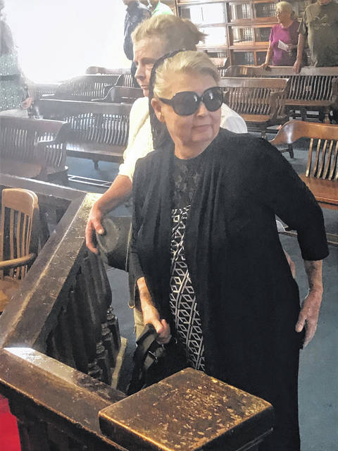 Flanked by a family member who has attended all of the Wagner hearings, Fredericka Wagner, wearing glasses, prepares to leave court after all charges against her were dropped Wednesday.