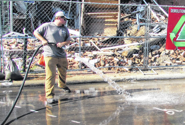 City of Hillsboro public works employee Evan Schelling is shown hosing down the street Thursday in front of a collapsed building on West Main Street. Schelling said it was in preparation for the Ohio Department of Transportation's plans for applying thermoplastic striping on the pavement.