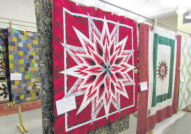 "This ""Feathered Star"" quilt from Sally Davis was one of the more than 100 quilts that were on display at Hillsboro High School Saturday during the annual Quilts of Highland County show. Quilter Jackie McLarty of Midland told The Times-Gazette that to make a quilt ""you take a good piece of cloth, cut it all up into little pieces, and then sew it all back together again."""
